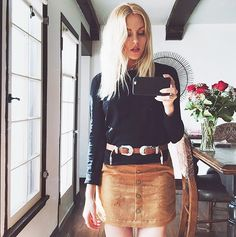 Shea Marie wears a black long sleeve top with a button-up suede skirts and brown belt.