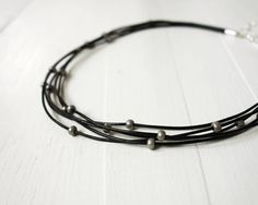 Leather choker necklace with silvery grey beads. Layered black leather cords have small light grey glass beads on them. The grey glass have a matte
