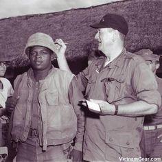 John Wayne signs PFC Wofford's helmet during his visit to the 3rd Bn., 7th Marines at Chu Lai in Vietnam.    Photo taken: June 1966