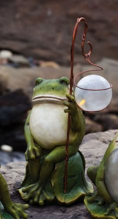 """Solar Staff Frog Statuary by Outdoor Decor. Save 37 Off!. $34.99. Made of polystone.. Solar-powered.. From the Solar Collection.. Great for yourself or as a gift!. 6"""" L x 5.25"""" W x 13.75"""" H. Relaxing on a hot summer day, this frog statuary smiles jovially. But he's got a hidden secret. Located just out of sight, a solar cell collects energy from the Sun, gathering energy to light a hidden LED through the night. A great addition to almost any garden, light up your life with this Solar Frog…"""