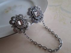 Sweater Guard / Sweater Clip: Repurposed Upcycled Silver Rhinestone Vintage Clip Earrings w/ Silver Tone Chain. Cardigan Clip. Blouse Clip.. $26.00, via Etsy.