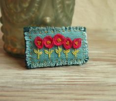 Pink and Teal Floral Embroidered Brooch. Needle craft is a traditional way for a community of women to be together. It offers an opportunity for passing down skills and a time for conversation.
