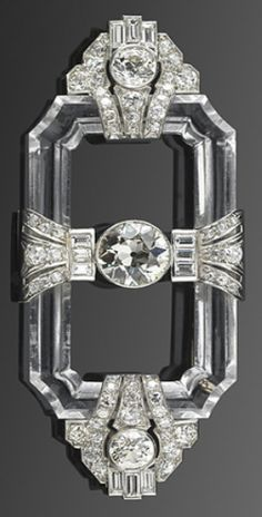 An Art Deco brooch, circa 1920s. A rock crystal frame connects platinum set geometric motifs centring upon an old European cut diamond. #ArtDeco #brooch