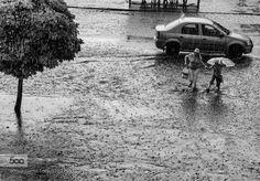 Summer rain. Woman with child runs across the street flooded by rain.