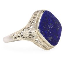 Across a deep blue sky of midnight blue lapis lazuli tiny flecks of gold point out the infinity of the universe. The 14 mm diameter lapis cabochon is oriented in a lozenge profile and set in an ornate mounting of open work 10k white filigree. The under gallery has pierced work in the form of a classical Greek frieze with the sides in a floral design among curved forms.   Date: Circa 1930.