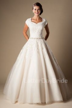 Fiona   Modest Wedding Dresses   Sleeves   LatterDayBride & Prom   SLC   Utah   Worldwide Shipping   LDS Bridal Gowns   This lovely modest ball gown features a stunning neckline and a beautiful lace pattern cinched in a dropped waist with a delicate beaded belt with gentle tendrils of lace floating delicately throughout the tulle skirt.    Gown available in White/Silver, Ivory/Silver or Champagne/Ivory/Silver    *Gown pictured in Champagne/Ivory/Silver