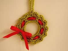 Aodrable Christmas wreath crochet ornament pattern with red ribbon and crocheted hanger.