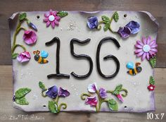 This whimsical hand made ceramic house number sign is a classic rectangle shape and personalised with your number. Choose pretty flowers,