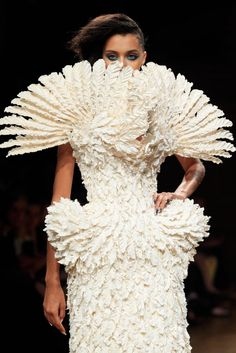 Graceful as a swan! This model presents a white feathered dress during the Serkan Cura show on July 10, 2014.