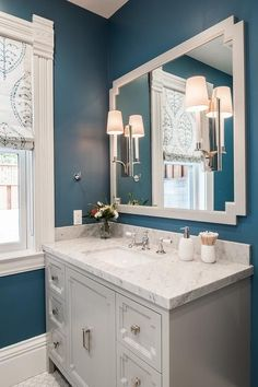 Chic bathroom features walls painted bold blue lined with a light gray art deco mirror lined with polished nickel 1 light sconces placed over a light gray washstand adorned with art deco cabinet doors topped with gray and white honed marble.
