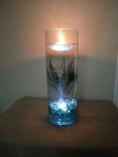 My Peacock theme wedding centre peices :) super cost effective too :):) two feathers, submersible light buried under iridescent turquoise, teal and clear stones and a floating candle :)