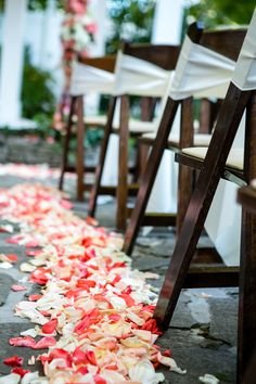 rose petal aisle runner - perfect! white chairs with navy and coral bows.