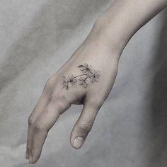 Fine line style cherry blossoms tattoo on the right hand. Tattoo artist: Kane Navasard