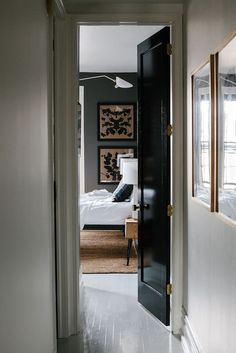 Black doors, brass hardware, seagrass, white bedding and lamps, b & w art, gray walls.