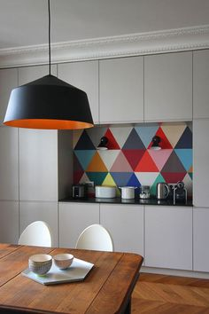 By Camille Hermand, a massive black pendant hangs above an antique dining table with white, modern chairs. A wall of cabinets is broken up with a colorful, triangular pattern behind the bar.