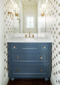 Blue and gold powder room features walls clad in Farrow & Ball Bumblebee Wallpaper lined with a blue washstand adorned with brass quatrefoil knobs topped with white marble placed under a frameless mirror illuminated by Bryant Sconces.