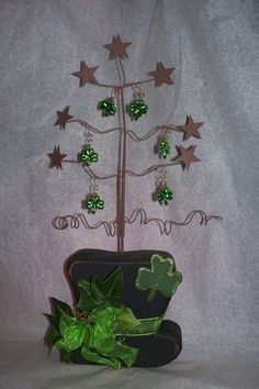 This tree has a wooden base with rusty star branches accented with ribbon,greenery and complete with miniature ornaments.