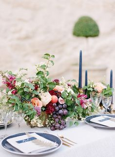 Vibrant and abundant wedding table with blue and gold details. Centerpiece with flowers and fruit.