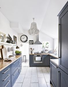 The grey units don't overwhelm this kitchen thanks to the high ceilings and bright white tiles and paint. Add a chandelier for an extra element of glamour!