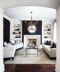This designer creates a comfortable feeling in this small space by: Painting the walls different colors, using color black, not putting anything in front of the fireplace, using shelves, putting large clock above fireplace.