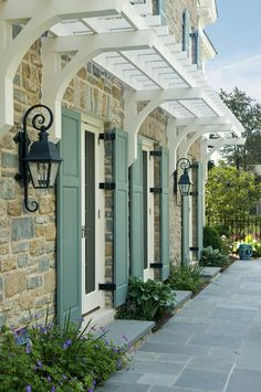 """Gotta love the lanterns, the pergola like """"awning"""", the stone and the shutter color.  Not that this is suitable for my red brick, but….one can dream."""