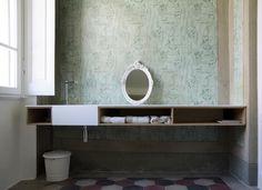 FASCINO COUNTRY: IL BAGNO Anche in bagno sono state riportate alla luce le decorazioni floreali delle pareti e le cementine d'epoca. Il mobile bagno, su disegno, e lo specchio instaurano un dialogo tra antico e moderno.