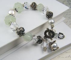 made with carved celadon jade beads, Swarovski crystal, and Bali and Hill Tribe sterling silver beads closing with a Bali silver clasp. Dangles of pearls and crystals are added the wrist for extra movement.