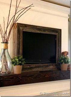 TV over fireplace with wooden frame.