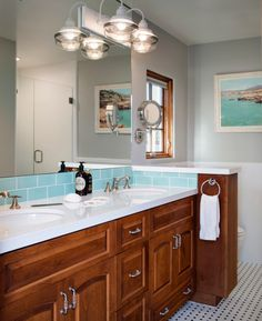bathroom sink with dark wooden cabinet, white top, white sink, blue tiles for backsplash, large mirror, round towel bar, glass lamps of Ideas for Towel Bar in Your Bathroom