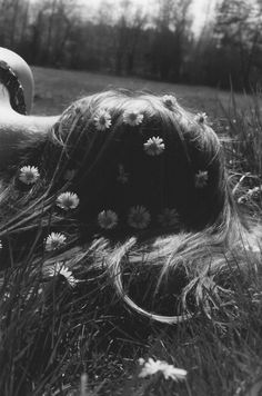 Daydreaming in the summer heat. She has become part of the field. daisies grow in her hair