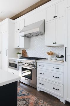 White beveled herringbone backsplash tiles brighten a cooktop design between whi. White beveled herringbone backsplash tiles brighten a cooktop design between white cabinets with oil rubbed bronze hardware and stainless steel appliances. Backsplash For White Cabinets, White Shaker Cabinets, White Kitchen Cabinets, Kitchen Redo, New Kitchen, Updated Kitchen, Kitchen Remodel, Dark Cabinets, Backsplashes With White Cabinets