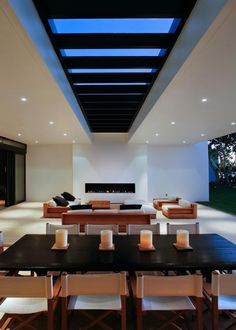 A contemporary dining room seats 10 comfortably and sleek, low seating around the fireplace creates a cozy conversation area. The covered patio features skylights above and is open to a lush backyard, so that the outdoors can be enjoyed even in bad weather.
