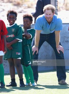 Prince Harry laughs with young girls during a visit to a Football for Hope session with Grassroots Soccer in Khayelitsha on November 30, 2015 in Cape Town, South Africa. Prince Harry is visiting South Africa as part of a Royal Tour that has included the Opening of a new Charity Centre for children in Lesotho (Sentebale's Mamohato Children's Centre) and includes stops in Durban, Cape Town, Kruger National Park and Johannesburg.