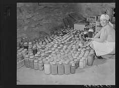 Josh Calahan's wife with some of her canned goods in the cellar of their new home. Southern Appalachian Project near Barbourville, Knox County, Kentucky, 1940