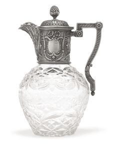 A Fabergé silver-mounted cut glass decanter, Moscow, circa 1895, the tapering glass body cut and engraved with a pattern of stars, swags, and bows, the neck mount cast and chased with oval shields surrounded by acanthus leaves and bow knots within beaded borders, the hinged, domed cover with leaf-wrapped pinecone finial rising from foliate calyx, the angular handle terminating in foliate ornament.