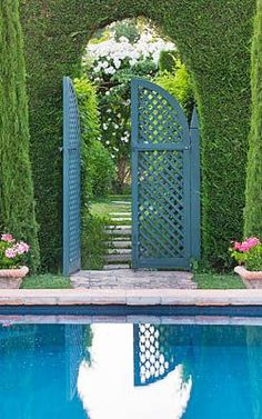 LES CONFINES, PROVENCE, FRANCE - DESIGNER: DOMINIQUE LAFOURCADE - SWIMMING POOL IN PORTUGUESE GARDEN AND VIEW THROUGH HEDGE AND BLUE TRELLIS GATE