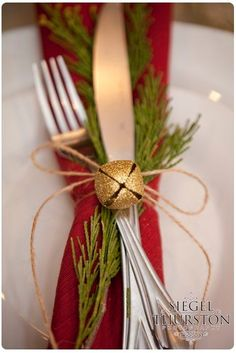 Table setting with red napkin and green garland tied up with twine and a gold bell by AudraL