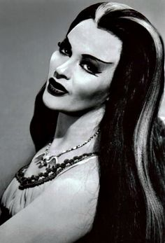 """Full Name: Lily Dracula Munster Age: Varies (but more than 137 years old) Birthplace: Transylvania Appearance: Vampirelike; silver streak in hair Siblings: Brother Lester and unnamed sister Abilities: Reading palms and cooking Occupation: Full-time housewife Preferences: Wears Chanel No. 13 perfume (""""the most exotic"""") Noticeable Qualities: Undying devotion to husband and family; sensitivity http://www.munsters.com/lily_munster.php Lily Munster, Yvonne De Carlo, Halloween Makeup, Halloween Costumes, Happy Halloween, Halloween Queen, Halloween Movies, Halloween Ideas, Spooky Halloween"""