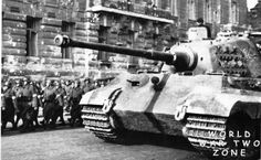 A King Tiger passing a column of soldiers on a city street.  (Sd.Kfz. 182)