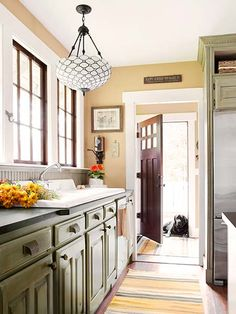In this kitchen remodel, the owners installed windows salvaged from a nearby house, DIY upper cabinets to match base ones found on Craigslist, and a vintage sink donated by a parent. The family's English lab, Hunter, guards the back door.