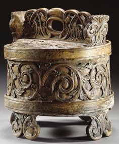 A BUTTER CHURN, NORWEGIAN, 18TH/19TH CENTURY, PROBABLY GUDBRANSDAL  pine, the scrolling acanthus leaf carved lid between two projecting handles, the coopered body similarly carved and held by concentric bands supported by four shaped feet