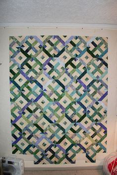 """sew five 2.5 strips together, then cut them into 10.5"""" squares. Put one square on top of the other, with the stripes going opposite ways (top square stripes go vertical, bottom square stripes go horizontal) and sew a quarter inch seam all around the perimeter. Then you cut the square in quarters diagonally, like a big X. This will give you 4 blocks, which you then play with on your design wall"""