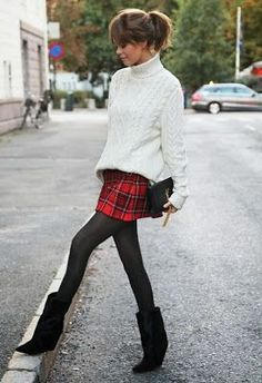 Red tartan skirt, white oversized cable knot jumper, black tights, black boots and black clutch bag.