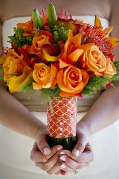 Lime green and orange are just meant to be together! Warm orange bouquet with lilies, pin cushion protea, roses and callas wrapped together with a modern print ribbon.
