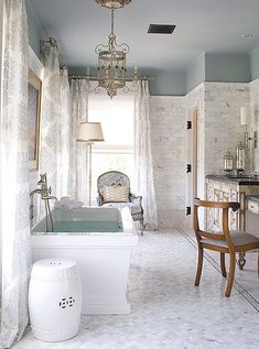 Stunning light gray marble master bath with a ceramic garden stool, chandelier and glamorous furnishings.