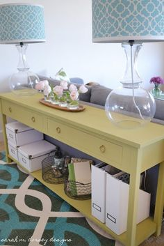 Hate these colors, like the idea of a skinny table covering up exposed back of couch