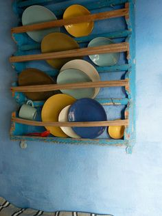 blue wall and colorful plates on rack.