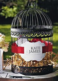"This birdcage is painted in an elegant black, giving it a timeless feel. Perfect to use as a card box or can be incorporated into any reception as a unique guest wishing well, sending the bride and groom well wishing for their life together.    Features and Facts:  16 1/2"" T and 10"" W  Decorations not included."