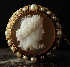 An 19th century agate cameo of Apollo in high relief depicting a classical bust of the god wearing a laurel wreath, set in a gold brooch enhanced with natural pearls and black enamel - French   c.1860