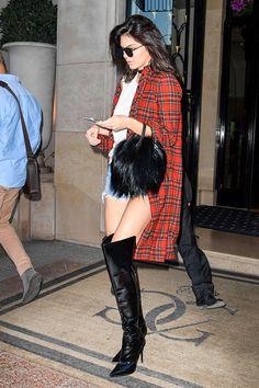 Kendall Jenner usa look básico com t-shirt, shorts jeans, camisa xadrez e botas over the knee de verniz